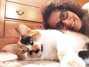 Leslea and Mitzi, her calico cat, lie on the floor to take a selfie